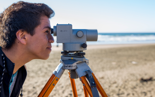 Student looking a surveying equipment on the beach